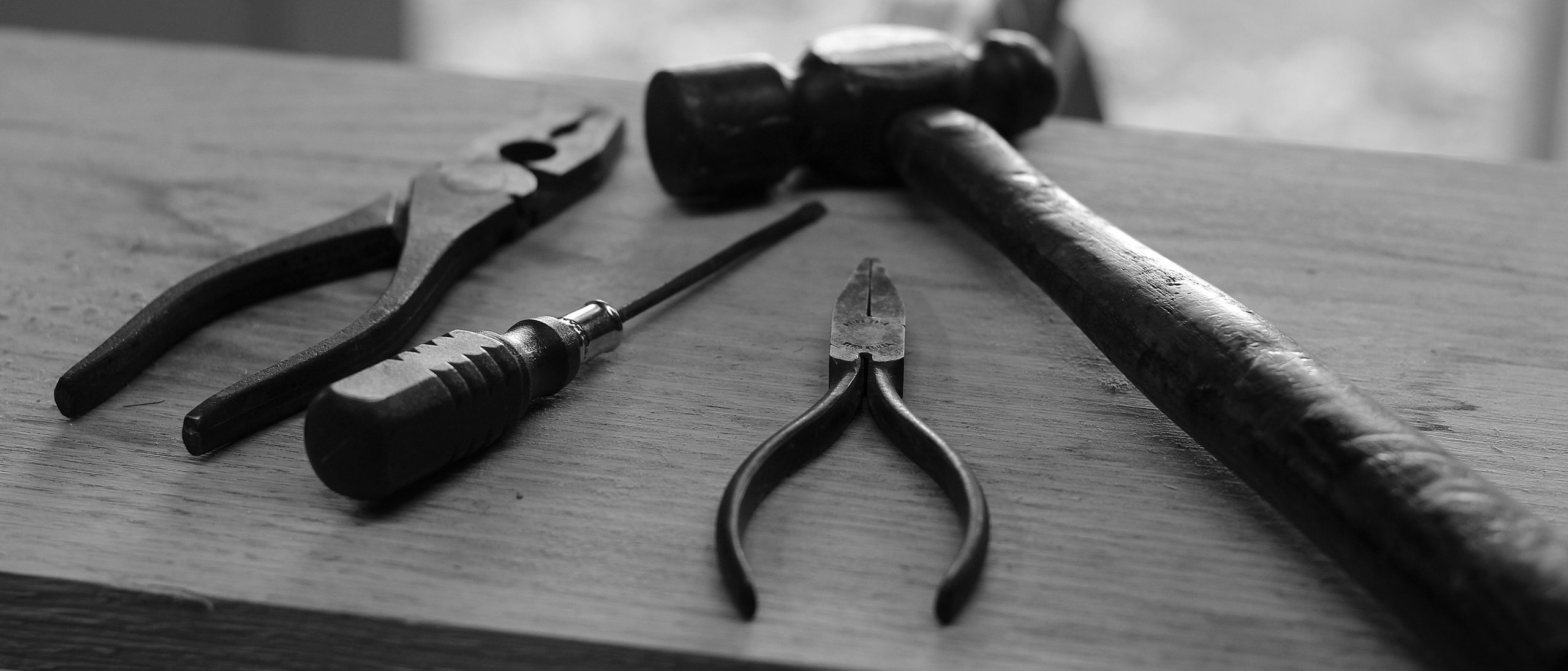 Black and White Photo of Tools on a Plank of Wood